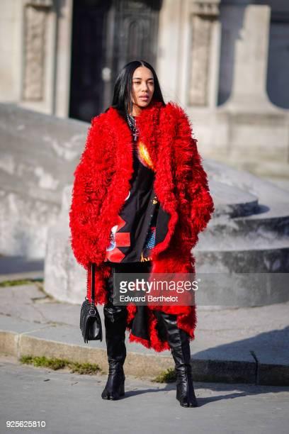 Aleali May wears a Chanel Boy bag a red fluffy faux fur coat black leather boots a flower print dress during Paris Fashion Week Womenswear...