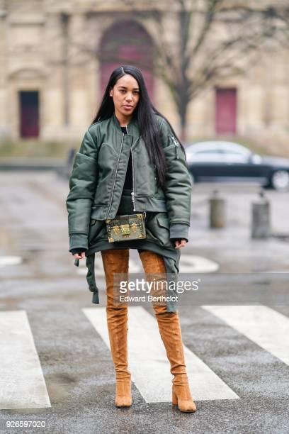Aleali may wears a green bomber jacket brown thigh high boots a Vuitton rigid bag outside Balmain during Paris Fashion Week Womenswear Fall/Winter...