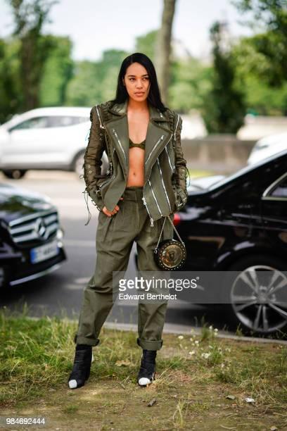 Aleali May wears a green khaki leather jacket green bras green pants a Balmain circular bag outside Balmain during Paris Fashion Week Menswear...