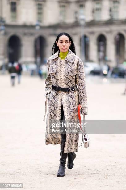 Aleali May wears a snake print trench coat a green turtleneck outside Kenzo during Paris Fashion Week Menswear F/W 20192020 on January 20 2019 in...