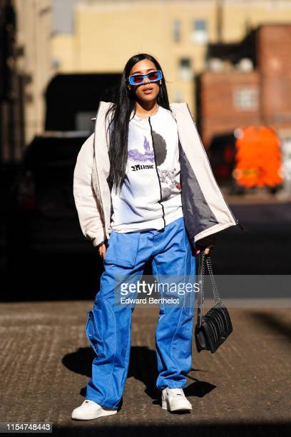 Aleali May wears blue sunglasses a white jacket a white top with printed drawings depicting a purple heart with wings and the word Music blue flare...
