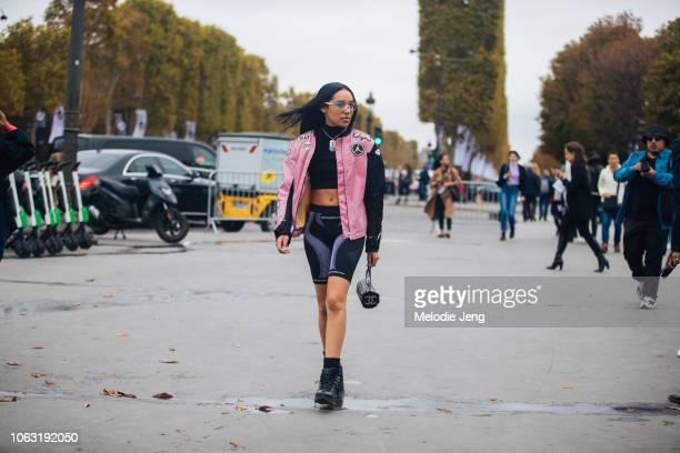 Aleali May wears clear Westward Leaning glasses a pink and black Jordan Jumpman jacket Chanel dog tag necklace black MISBHV biker shorts a small...