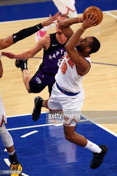Alec Burks of the New York Knicks attempts a shot against the Toronto Raptors at Madison Square Garden on April 11, 2021 in New York City. The Knicks...