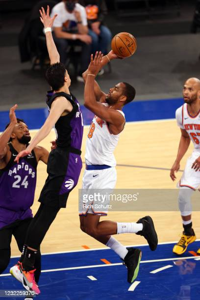 Alec Burks of the New York Knicks attempts a shot as Yuta Watanabe of the Toronto Raptors defends at Madison Square Garden on April 11, 2021 in New...