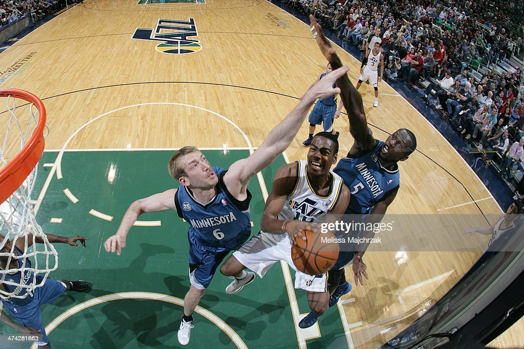Alec Burks #10 of the Utah Jazz drives to the basket against Robbie Hummel #6 and Gorgui Dieng #5 of the Minnesota Timberwolves at EnergySolutions Arena on February 22, 2014 in Salt Lake City, Utah.