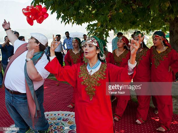 Alec Chiarong a tour agent from Singapore dances with Kashmiri folk dancers in traditional attire on the bank of Dal lake during the Shikara boats...