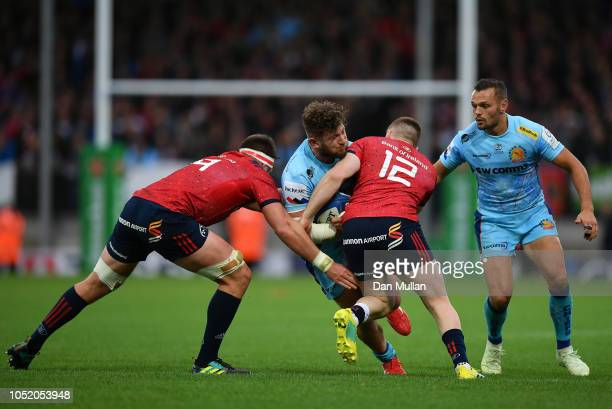 Alec Hepburn of Exeter Chiefs is tackled by Billy Holland and Rory Scannell of Munster during the Heineken Champions Cup match between Exeter Chiefs...