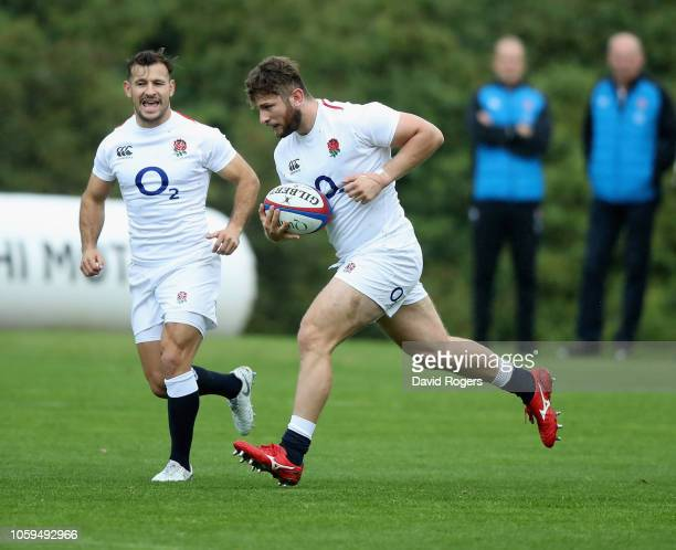 Alec Hepburn runs with the ball watched by Danny Care during the England captain's run at Pennyhill Park on November 9 2018 in Bagshot England