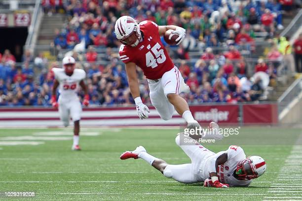 Alec Ingold of the Wisconsin Badgers jumps over Jalin Burrell of the New Mexico Lobos during the first half at Camp Randall Stadium on September 8...