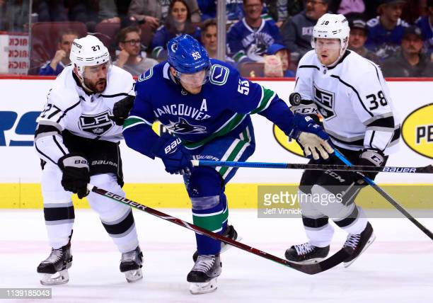Alec Martinez and Carl Grundstrom of the Los Angeles Kings and Bo Horvat of the Vancouver Canucks watch a loose puck during their NHL game at Rogers...