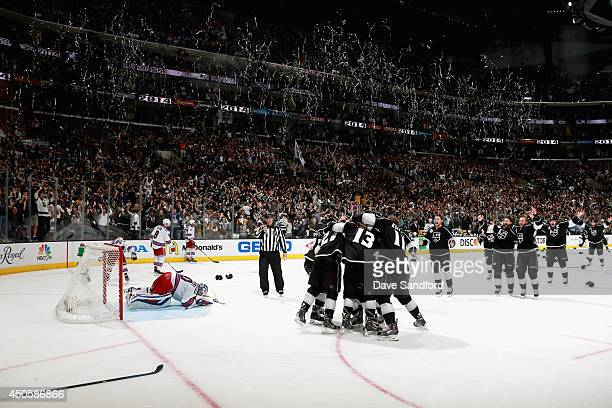 Alec Martinez and the Los Angeles Kings celebrate after scoring the gamewinning double overtime goal on goaltender Henrik Lundqvist of the New York...
