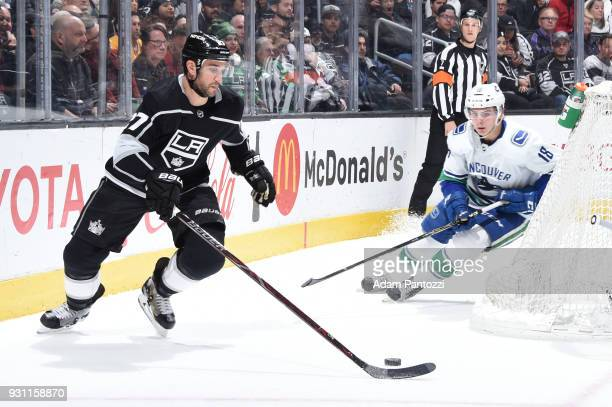 Alec Martinez of the Los Angeles Kings handles the puck against Jake Virtanen of the Vancouver Canucks at STAPLES Center on March 12 2018 in Los...