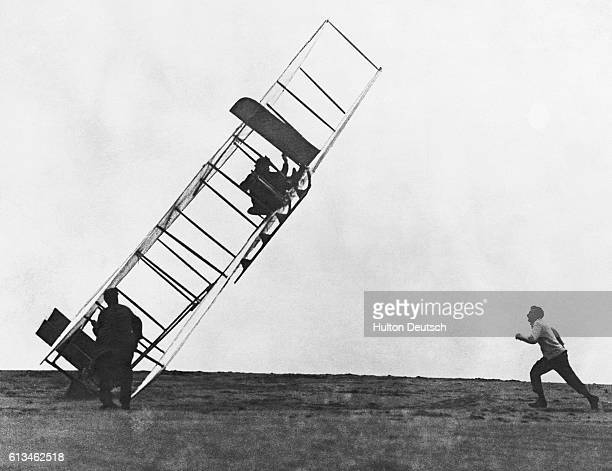 Alec Ogilvie runs to assist Wilbur Wright trying to help his brother Orville out of a glider which did not land properly