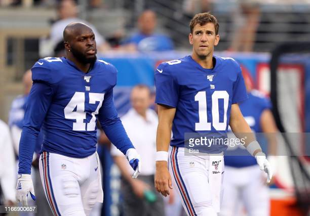 Alec Ogletree and Eli Manning of the New York Giants walk out for the coin toss before the game against the New York Jets during a preseason matchup...