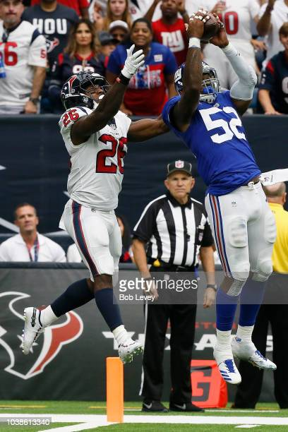 Alec Ogletree of the New York Giants intercepts the ball intended for Lamar Miller of the Houston Texans in the fourth quarter at NRG Stadium on...