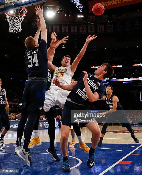 Alec Peters of the Valparaiso Crusaders is blocked by Jakob Heartsick and Zac Seljaas of the Brigham Young Cougars during their NIT Championship...