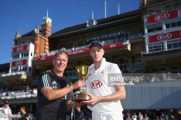 Alec Stewart and Morne Morkel of Surrey celebrate with the Specsavers County Championship Division One Cup during Day Four of the Specsavers County...