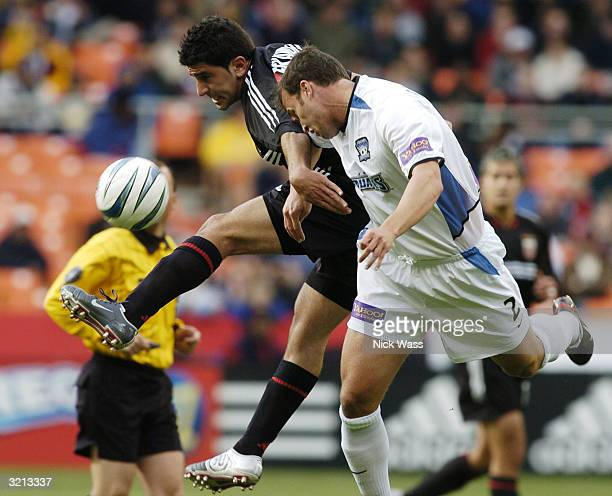 Alecko Eskandarian of DC United kicks against Eddie Robinson of the San Jose Earthquakes during the first half at RFK Stadium April 3 2004 in...