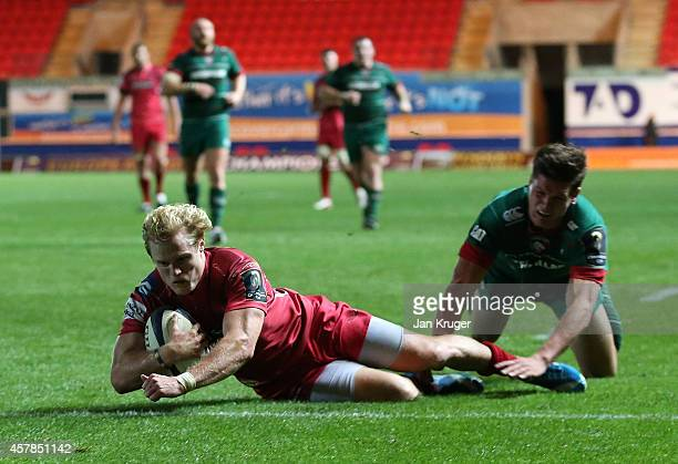 Aled Davies of Scarlets dives over the line for his try under pressure from Freddie Burns of Leicester Tigers during the European Rugby Champions Cup...