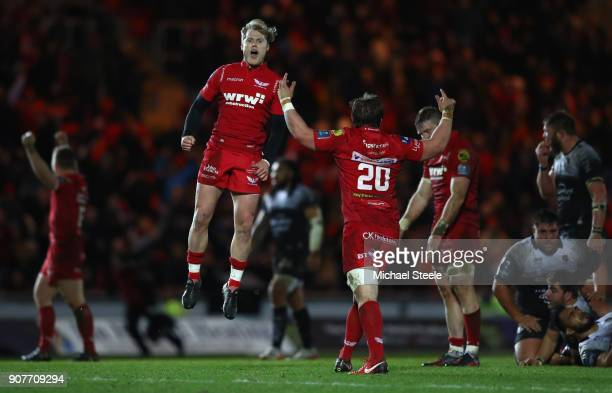 Aled Davies of Scarlets leaps into the as he celebrates at the final whistle and his sides 30-27 victory with Will Boyde during the European Rugby...