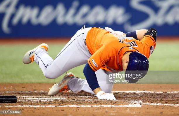 Aledmys Diaz of the Houston Astros reacts after being struck by a pitch from Zack Godley of the Toronto Blue Jays in the seventh inning during a MLB...