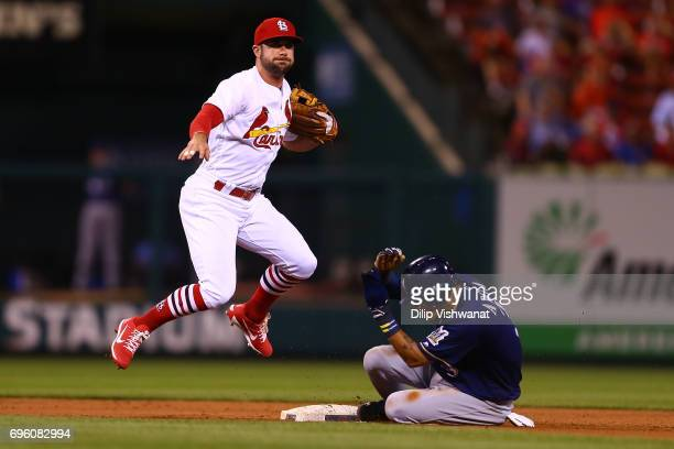 Aledmys Diaz of the St Louis Cardinals attempts to turn a double play over Orlando Arcia of the Milwaukee Brewers in the sixth inning at Busch...