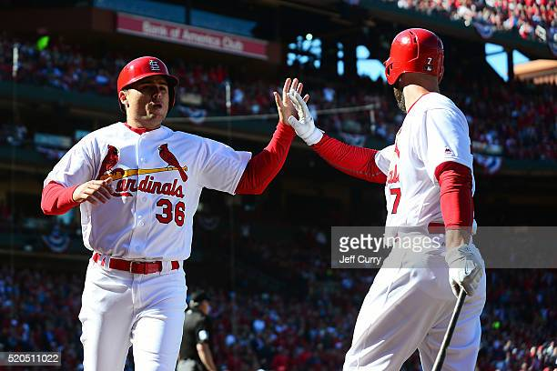 Aledmys Diaz of the St Louis Cardinals celebrates with Matt Holliday after scoring in the second inning against the Milwaukee Brewers during the home...