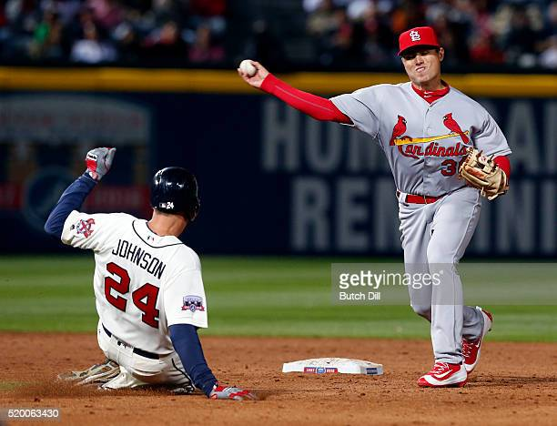 Aledmys Diaz of the St Louis Cardinals throws to first for the double play as Kelly Johnson of the Atlanta Braves slides into second base during the...