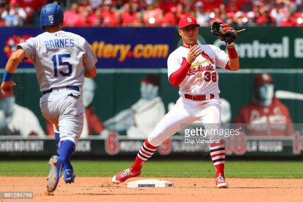 Aledmys Diaz of the St Louis Cardinals turns a double play against Austin Barnes of the Los Angeles Dodgers in the seventh inning at Busch Stadium on...