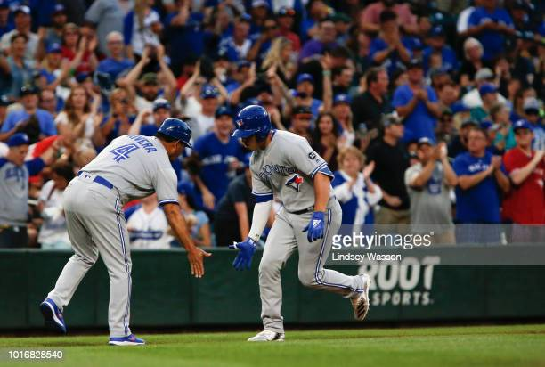 Aledmys Diaz of the Toronto Blue Jays celebrates his home run against James Paxton of the Seattle Mariners in the fifth inning with third base coach...