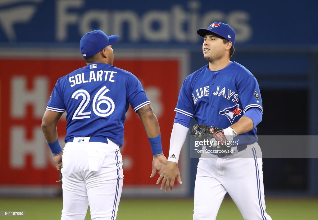 Aledmys Diaz #1 of the Toronto Blue Jays celebrates their victory with Yangervis Solarte #26 during MLB game action against the Chicago White Sox at Rogers Centre on April 2, 2018 in Toronto, Canada.