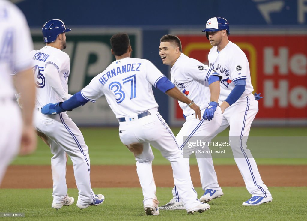 Aledmys Diaz #1 of the Toronto Blue Jays is congratulated by teammates after hitting a game-winning RBI single in the tenth inning during MLB game action against the Baltimore Orioles at Rogers Centre on June 7, 2018 in Toronto, Canada.