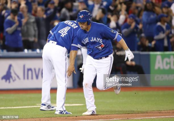 Aledmys Diaz of the Toronto Blue Jays is congratulated by third base coach Luis Rivera as he circles the bases after hitting a solo home run in the...