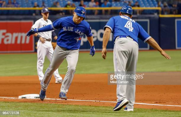 Aledmys Diaz of the Toronto Blue Jays is congratulated by third base coach Luis Rivera after his home run in the eighth inning of a baseball game...