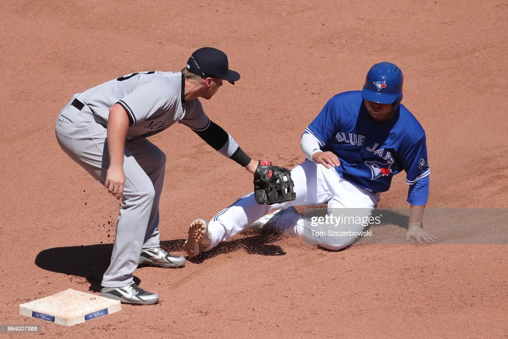 Aledmys Diaz #1 of the Toronto Blue Jays is tagged out by Brandon Drury #29 of the New York Yankees as he is caught stealing after being picked off in the eighth inning during MLB game action at Rogers Centre on July 8, 2018 in Toronto, Canada.