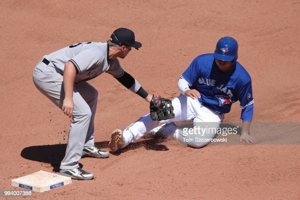 Aledmys Diaz of the Toronto Blue Jays is tagged out by Brandon Drury of the New York Yankees as he is caught stealing after being picked off in the...