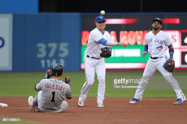 Aledmys Diaz of the Toronto Blue Jays turns a double play in the third inning during MLB game action as Jose Iglesias of the Detroit Tigers slides...