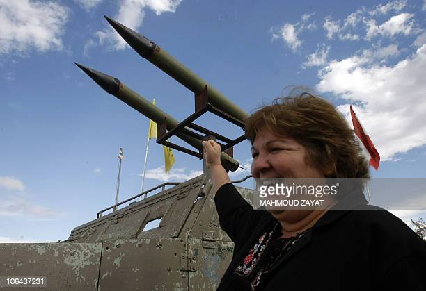 Aleida Guevara daughter of Ernesto 'Che' Guevara poses next to a model of a tank and rockets made by Hezbollah during a tour in the southern Lebanese...