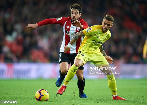 Aleix Garcia of Girona FC competes for the ball with Benat Etxebarria of Athletic Club during the La Liga match between Athletic Club and Girona FC...