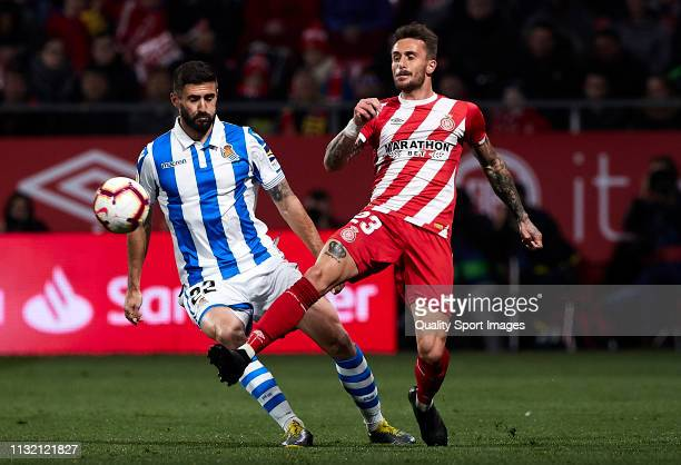 Aleix Garcia of Girona FC competes for the ball with Raul Navas of Real Sociedad during the La Liga match between Girona FC and Real Sociedad at...