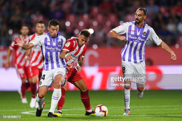 Aleix Garcia of Girona FC competes for the ball with Ruben Alcaraz and Borja Fernandez of Real Valladolid CF during the La Liga match between Girona...