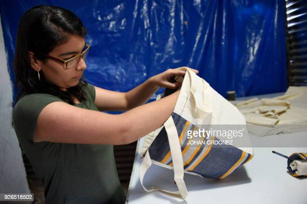 Alejandra Marroquin checks a cotton bag inspired in Mayan costumes made within an attempt to put a curb on the abuse of plastic usage in Perez...