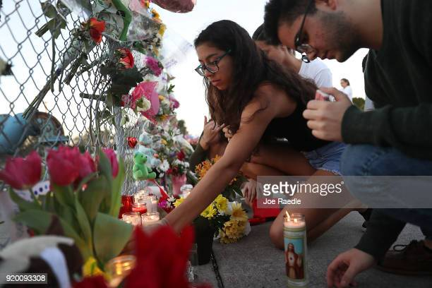 Alejandra Martinez a junior at Marjory Stoneman Douglas High School lights candles in a makeshift memorial setup in front of the school on February...