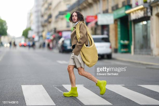 "Alejandro Acero @alexacerov wears a white turtleneck pullover, a brown oversized jacket with flared sleeves from Bottega Veneta, a beige / ""tapioca..."
