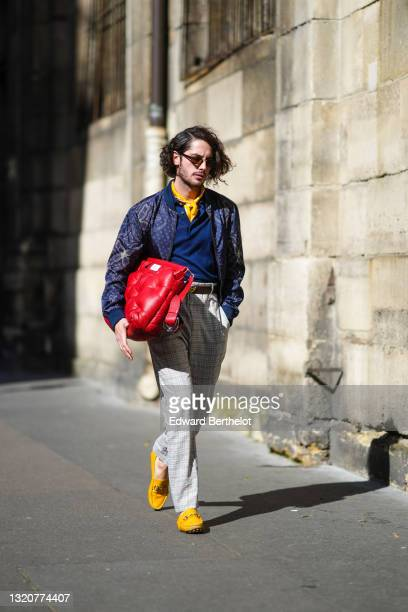 Alejandro Acero wears sunglasses, a yellow with white scarf, a blue polo Etro shirt, a blue with white and brown pattern zipper Etro jacket, a brown...