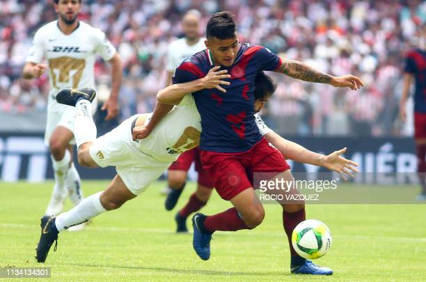 Alejandro Arribas of Pumas vies for the ball with Alexis Vega of Guadalajara during the Mexican Clausura 2019 tournament football match at the...