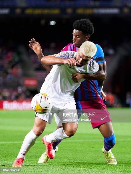 Alejandro Balde of FC Barcelona competes for the ball with Monchu Rodriguez of Granada CF during the La Liga Santander match between FC Barcelona and...
