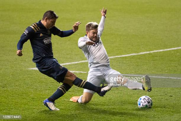 Alejandro Bedoya of Philadelphia Union passes the ball against Kelyn Rowe of New England Revolution in the second half during Round One of the MLS...