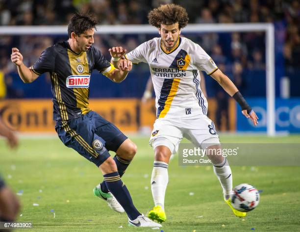 Alejandro Bedoya of Philadelphia Union passes the ball as Joao Pedro of Los Angeles Galaxy defends during Los Angeles Galaxy's match against...