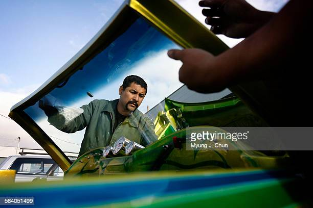 Alejandro 'Chino' Vega installs the windshield on his 1979 Chevrolet Monte Carlo on Friday morning after working all night in preparation for the...